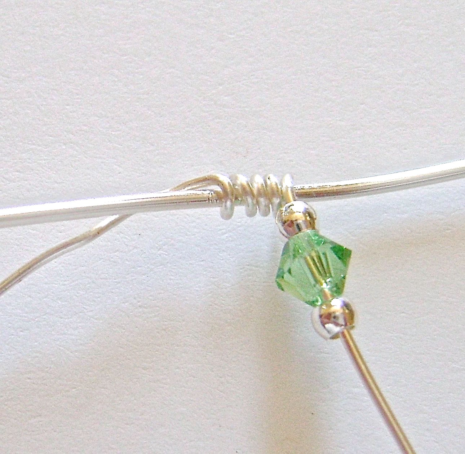 step 3 - Add a silver bead, bicone, and another silver bead to the right side wrapping wire.