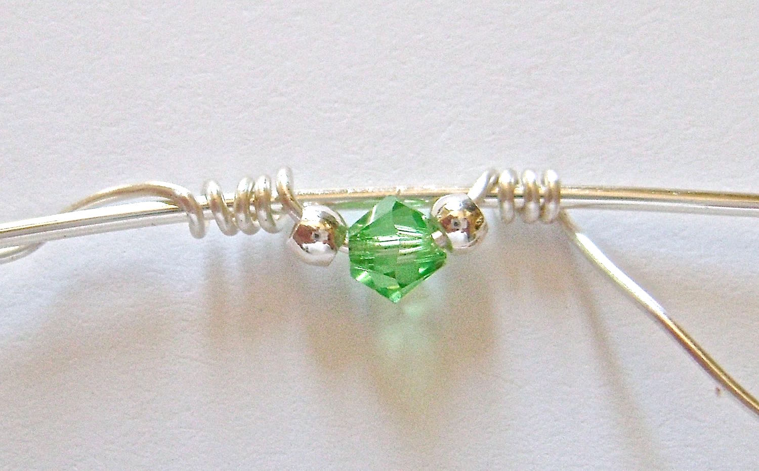"""step 4 - Hold the beads against the wire to keep them from moving and wrap the free end around the 5"""" wire four times."""