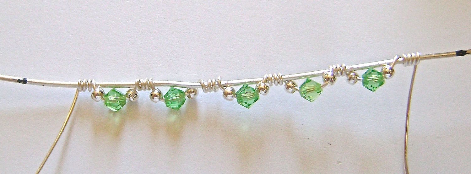 """step 5 - Continue wrapping and adding beads until you have three sets attached to the 5"""" wire. Do the same with the left side wrapping wire adding only two sets for a total of five sets."""