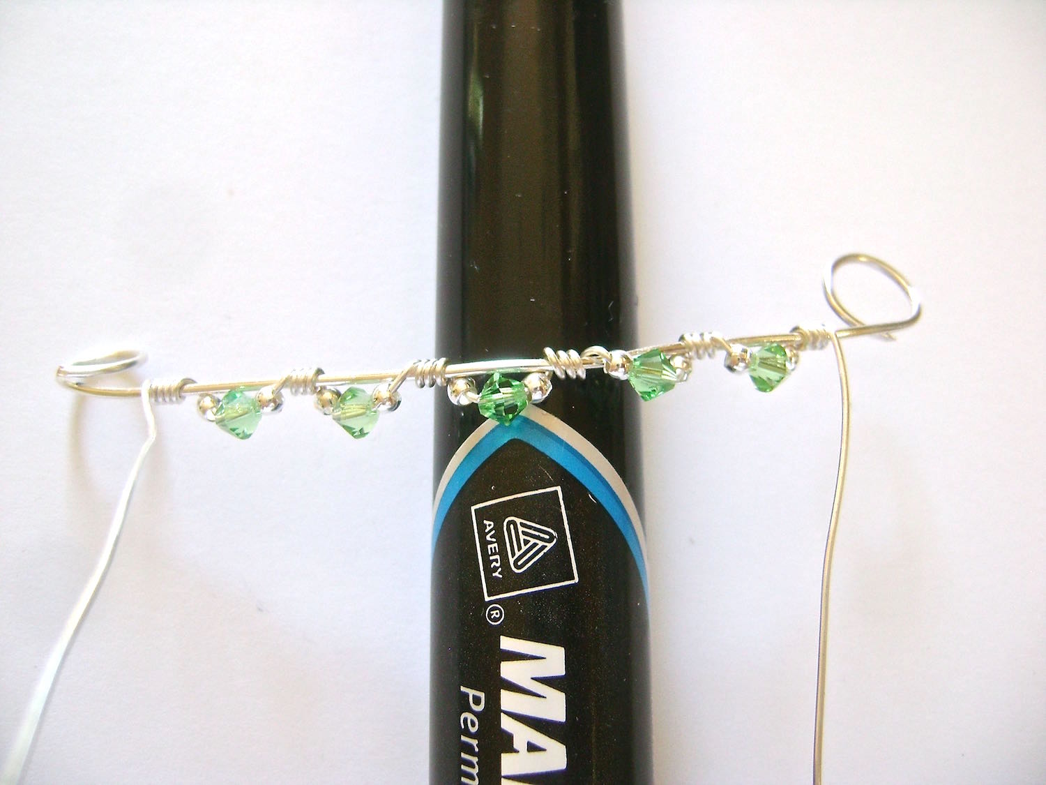 """step 8 - Bend the 5"""" wire against a large magic marker with the center bicone in the center of the marker."""