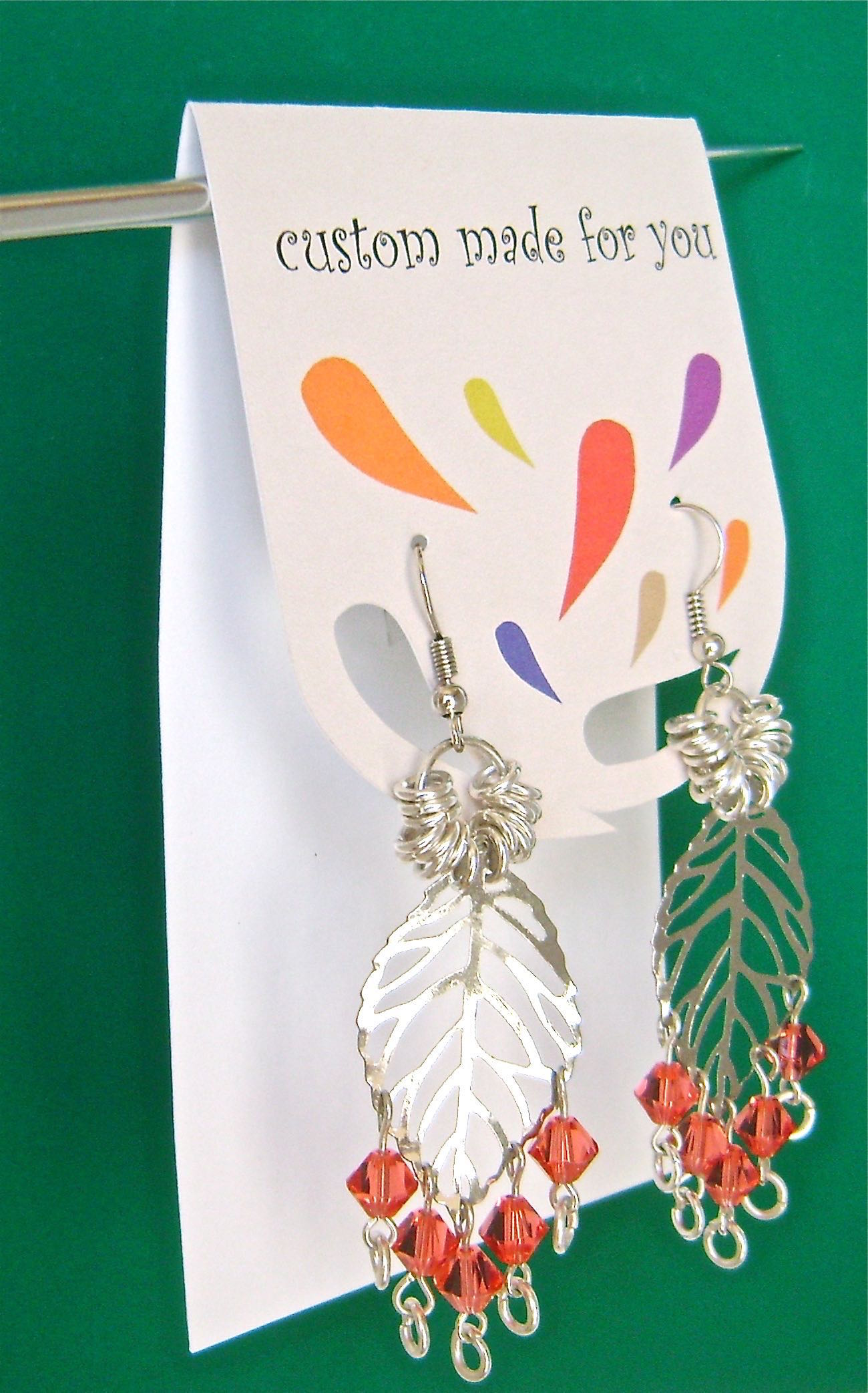 step 3 - Fold the printed flap with a sharp crease. Insert the earring wires in the holes and secure them on the back with earring wire clutches. At craft boutiques, earring cards are an easy way to display your work.  Just hang the cards on a stiff wire.
