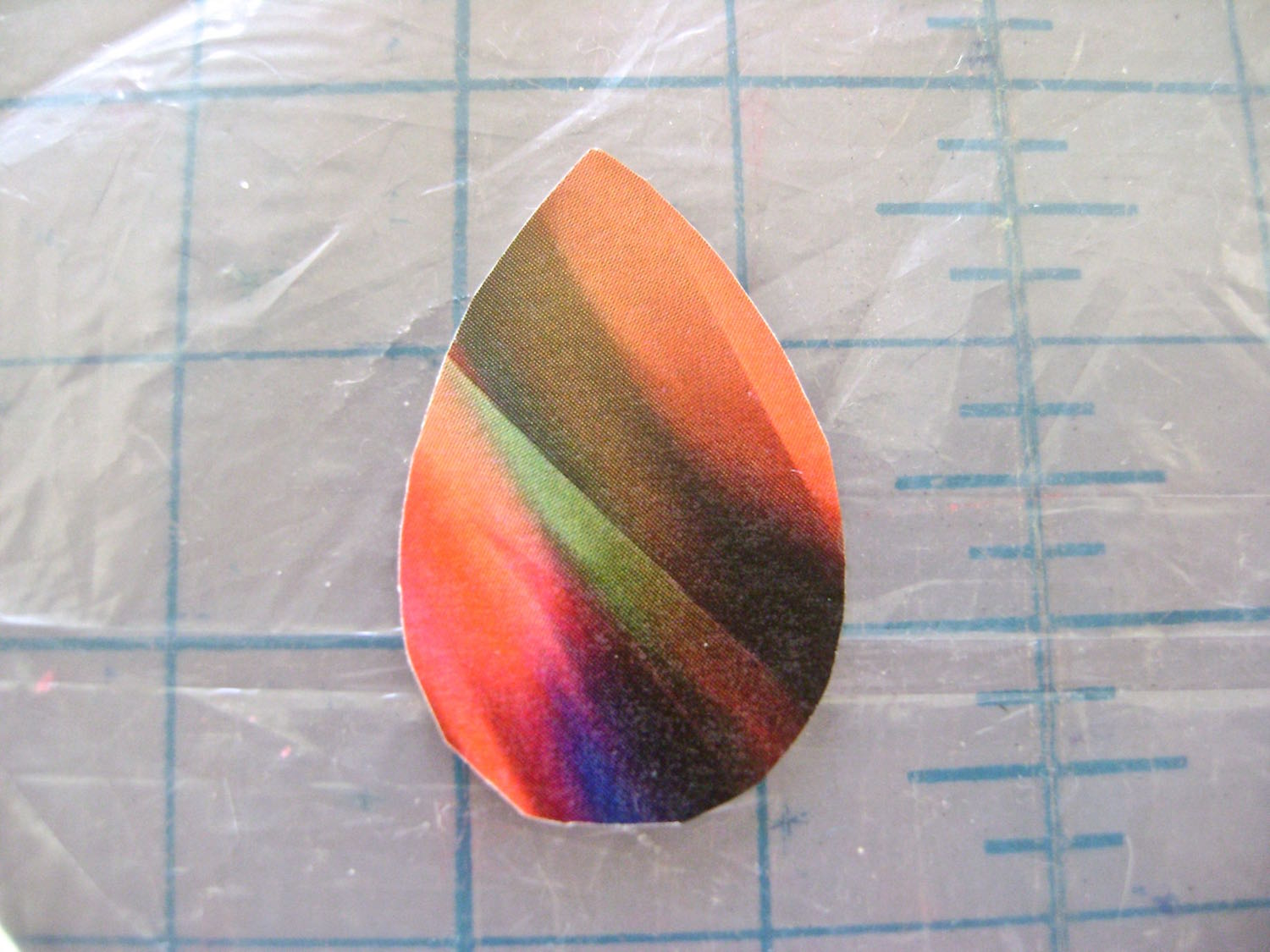 step 5 - Cut out the teardrop shape from your image.  step 6 - Hold the color image behind the glass.  The fit is accurate if the paper is slightly inside the border of the glass when you view it from the back side, and the image appears to reach to all edges when you look at it from the front.  step 7 - Clean both sides of the glass thoroughly.  Pour some Fast Finish into a container.   Dampen a one-inch wide brush then squeeze out the moisture in a towel.  Sponge brushes will cause bubbles with this product so choose a bristle brush.