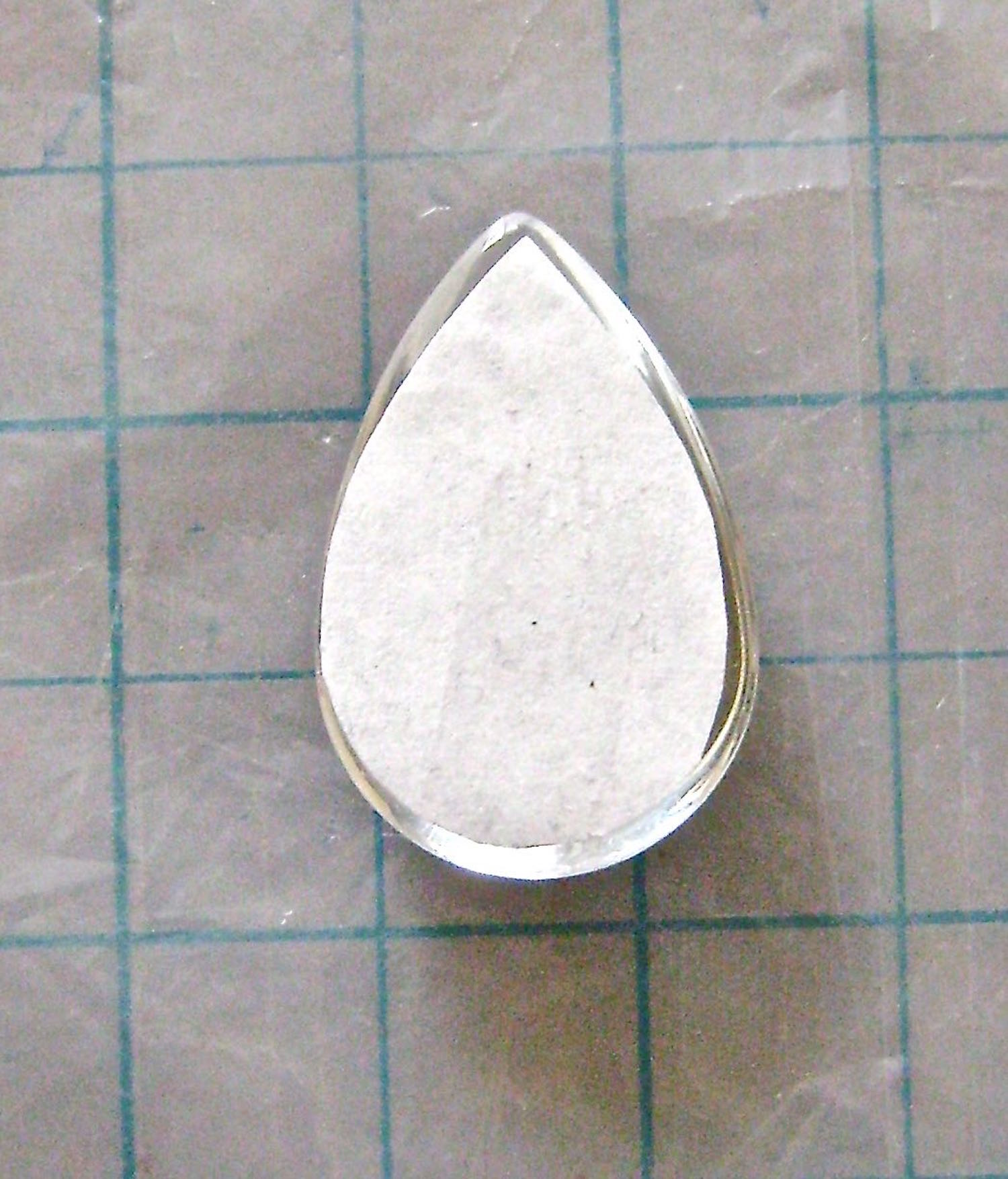 step 9 - With the color side down, set the paper in place on the glass leaving a tiny margin outside the paper edge.  Work quickly.  Like the name suggests, Fast Finish dries super fast. The good news is, if you make a mistake in placement you can start over.  Put the pendant in hot tap water with detergent for a few minutes.  The glue and paper will slide right off and you'll have a clean piece of glass for your next try.