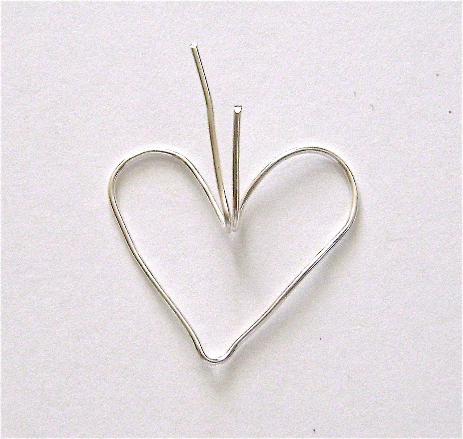 step 3 - Bend both wires to an angle where they meet in the center.  The edge of a metal ruler is ideal for this. Create a 45 degree angle with the wires pointing up from the heart.  These wires will form the pendant loop later.