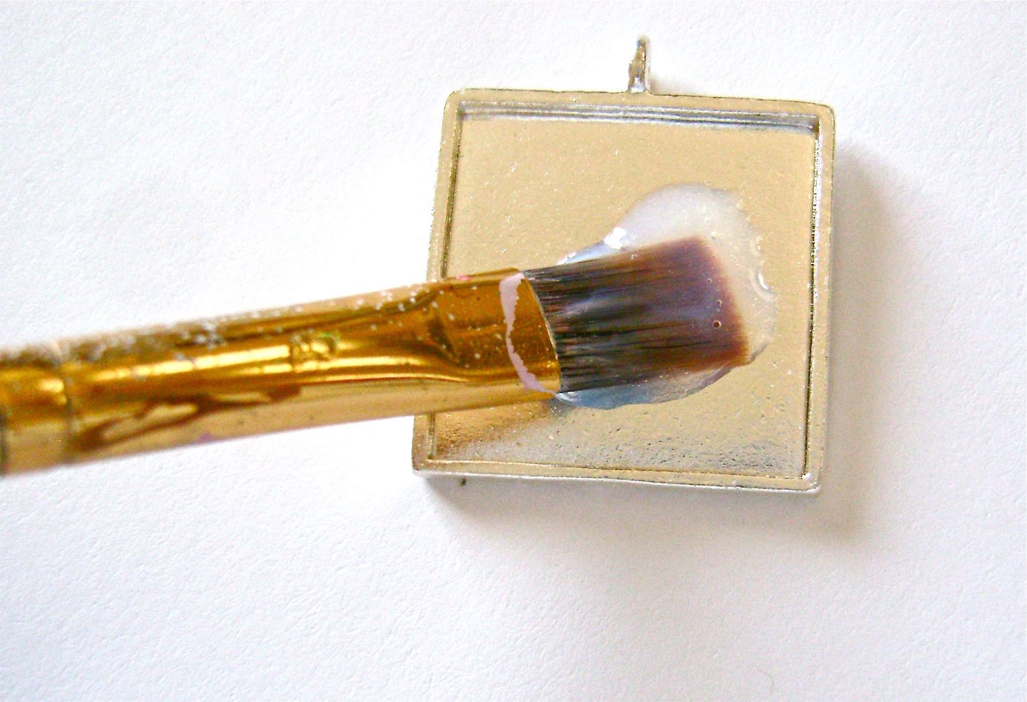 step 2 - Fill a small container with Diamond Glaze.  Using a brush, apply a light coat of glaze to the inside of the pendant frame.  Be sure to get into the corners.