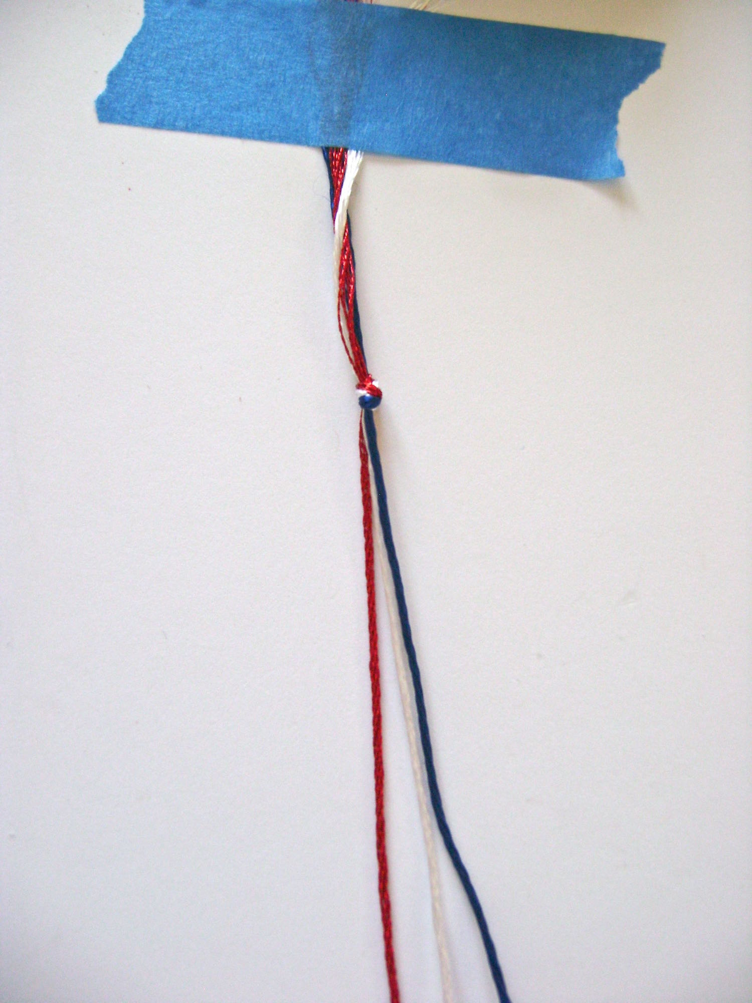 step 5 - Gather three strands of embroidery floss, red, white, and blue and knot them together. Tape the knotted end to the work surface.