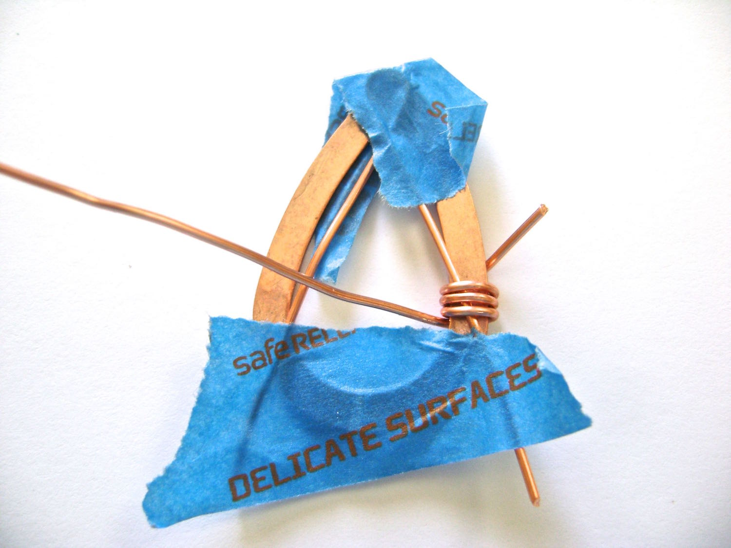 """step 3 - Cut a piece of wire to measure 6"""" long. Starting from the backside of the teardrop wrap it around to the right side three times."""