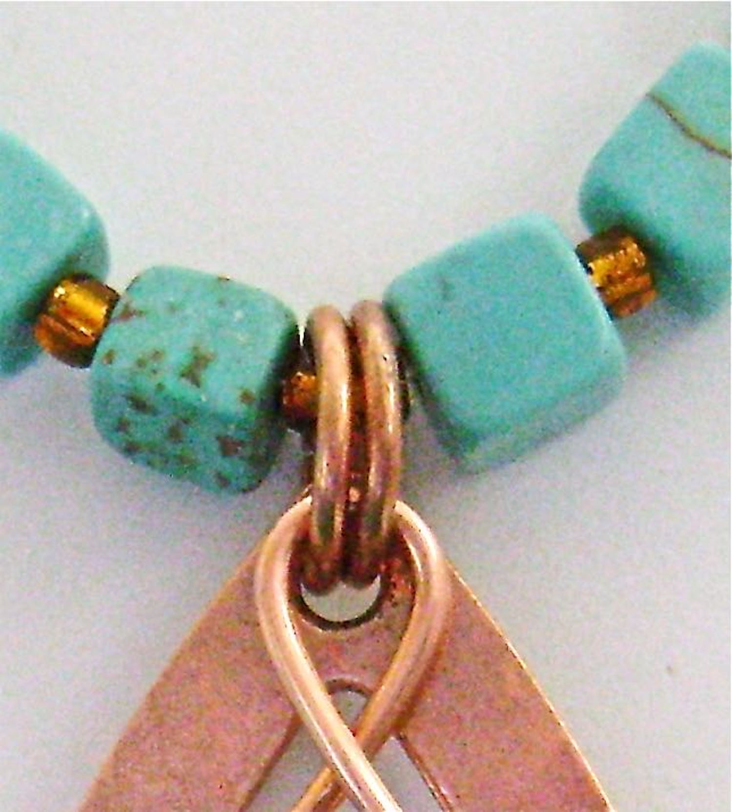 step 7 - Attach two copper jump rings to the teardrop and loop of the decorative wire.