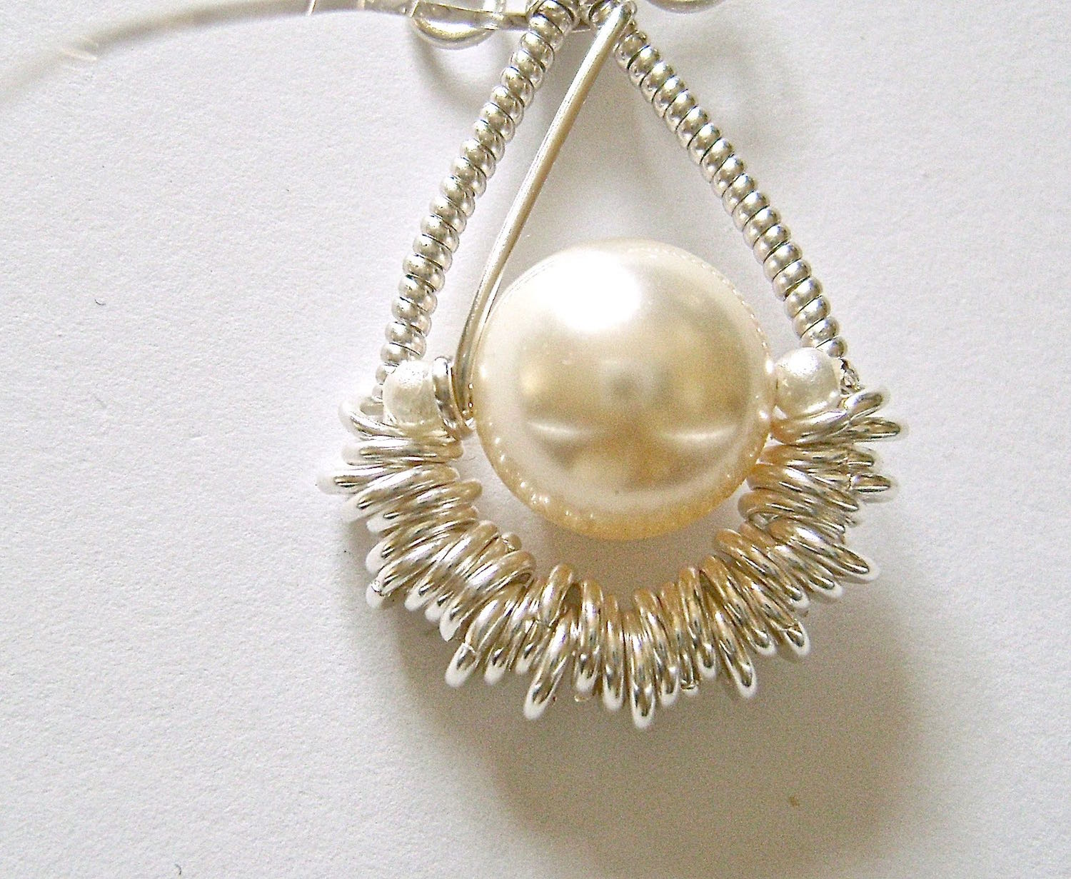 step 11 - Bring the wires down on both sides and wrap them twice between the large pearl and seed pearls.  Cut off the excess wire.