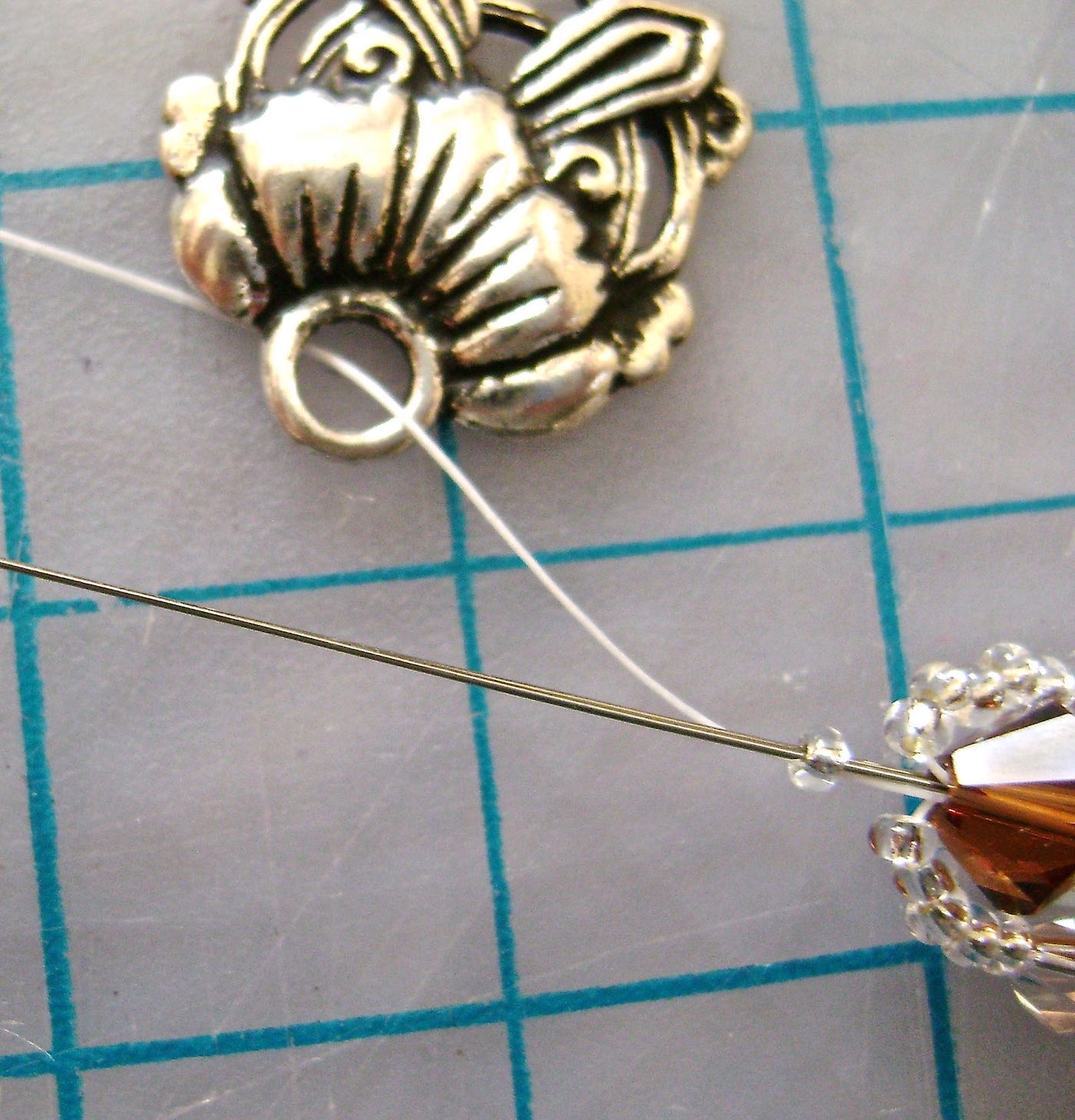 step 9 - Add one half of the clasp of your choice, then bring the needle back through the seed bead and up through the next two 6MM beads.