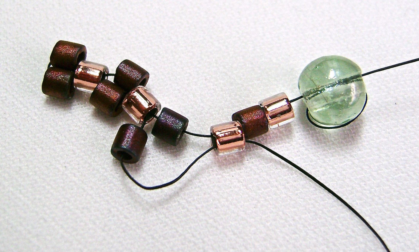 step 5 - Add another dark bead and pass through the third light bead.