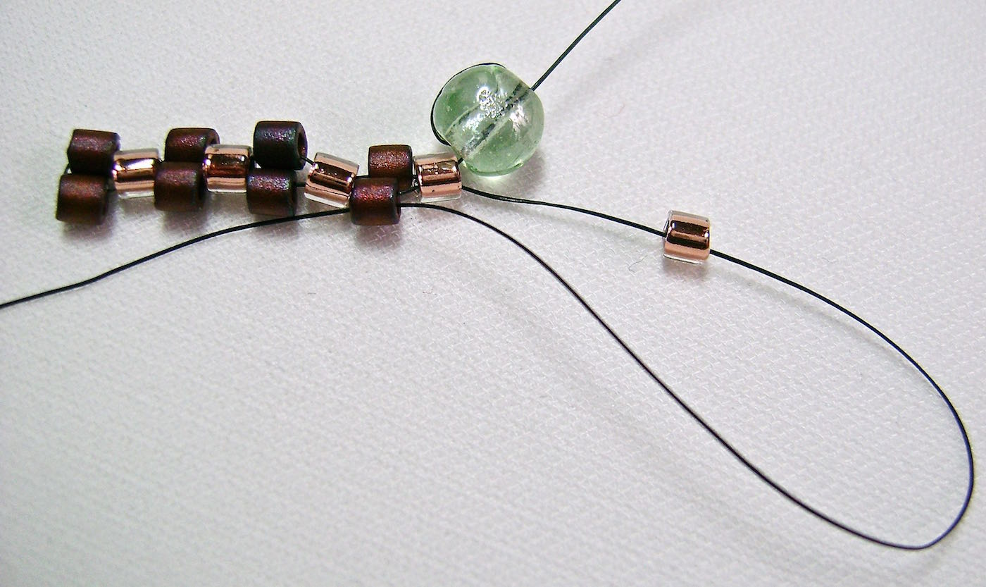 step 7 - Thread on a light bead to begin the next row. In this row you will be adding light beads, passing the needle through the dark beads of the previous row. You continue to alternate from light beads to dark in each row until your reach the length bracelet you need. This is the entire magic of the peyote stitch. If you're ever unsure of what color bead you should be adding at the end of the row, look at the color of the bead on that side of the bracelet. Because you're designing with an even number of beads, the strip of beads on one side of the bracelet will be the opposite of the beads on the other.