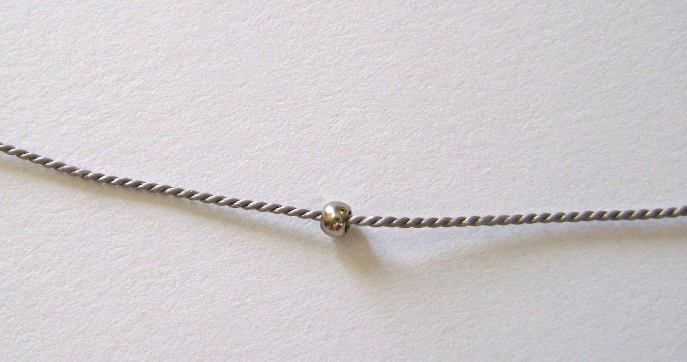 step 1 - Place a crimp bead onto the bead cord.