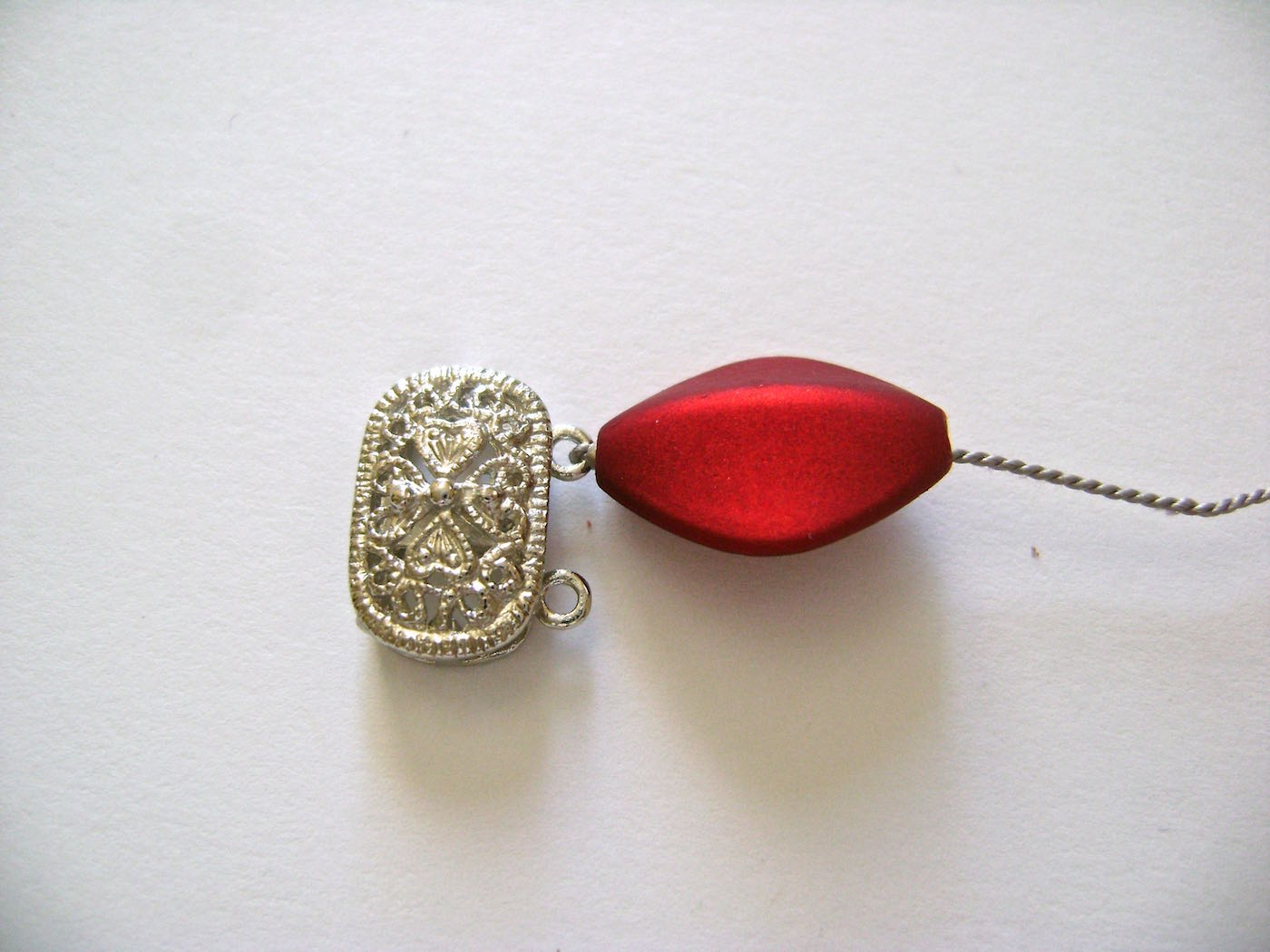 step 4 - Slip a red bead onto the cord and push it toward the clasp. The bead will cover the crimp.