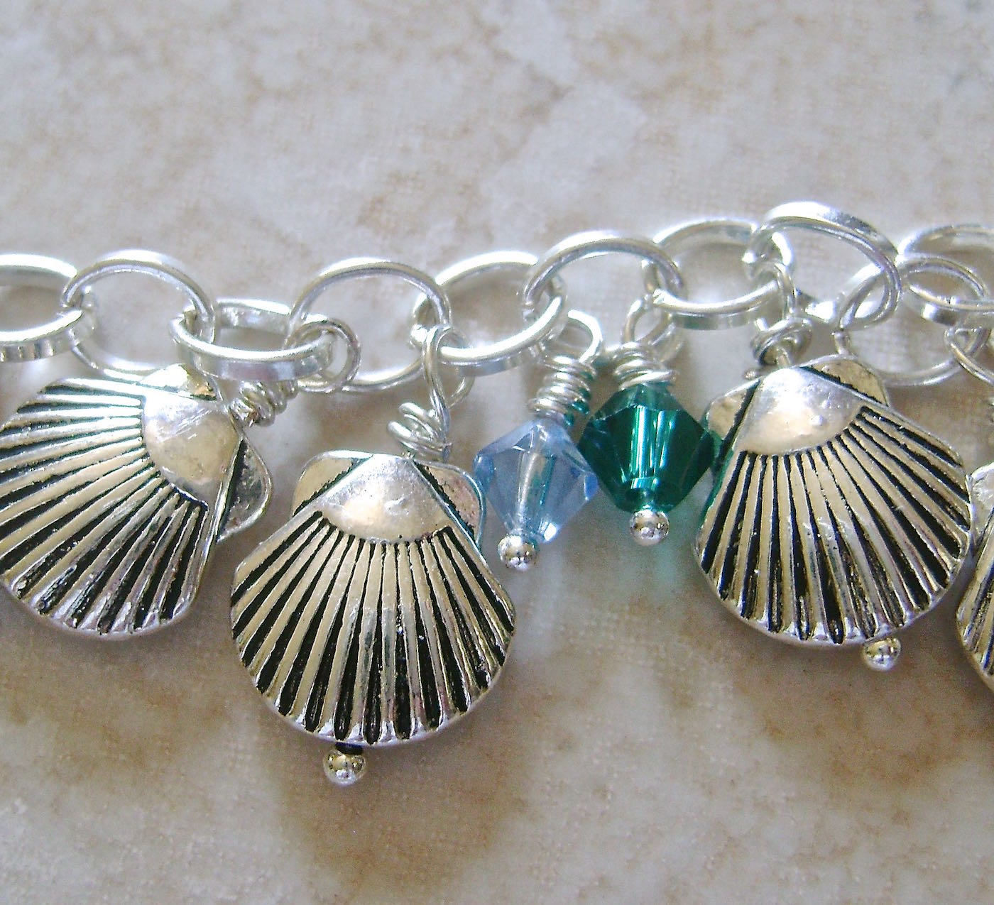 step 8 - Create  wrapped loops  for 13 teal and 13 blue crystals. Open the empty chain link between the shells and attach one of each color crystal.