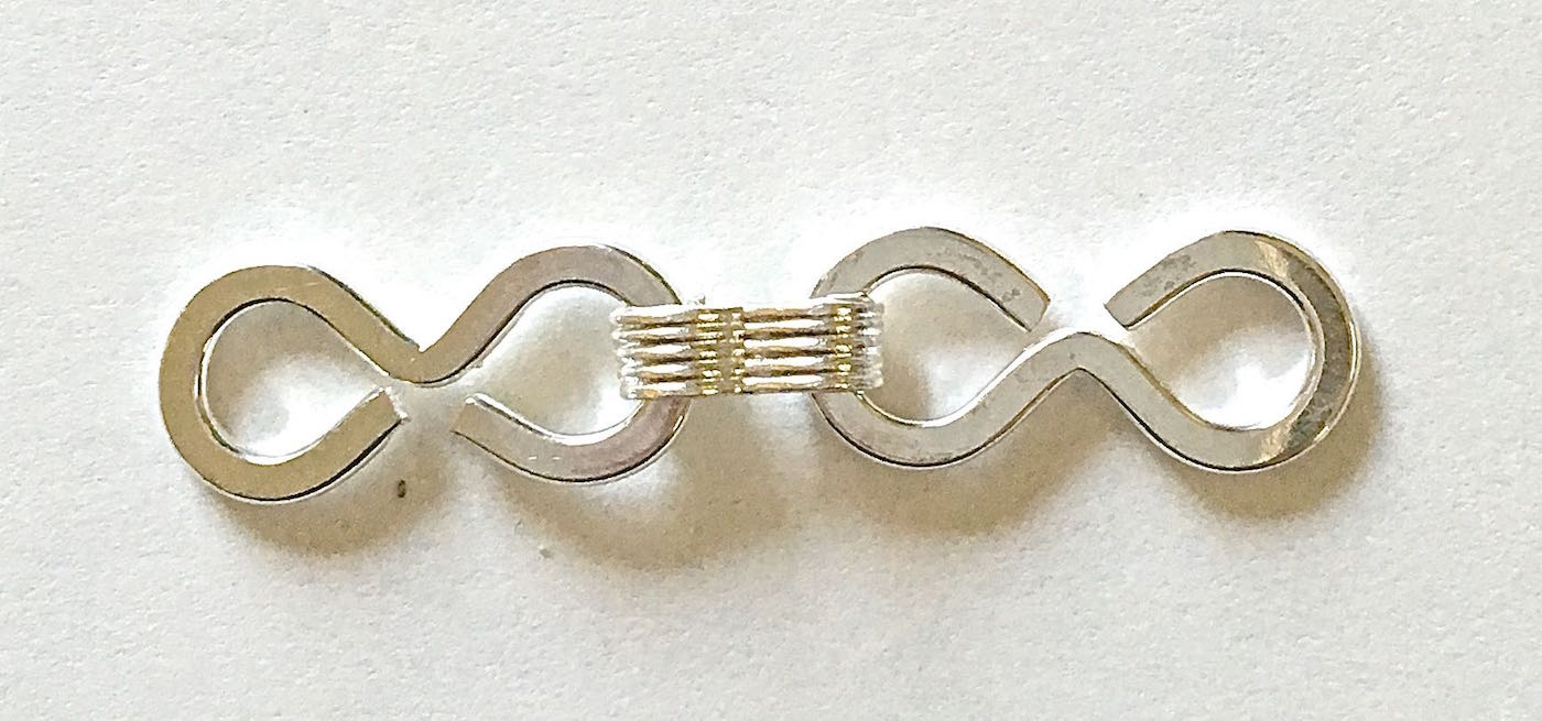 step 2 - Slip a figure eight onto the other side and use the the pliers to close it. Continue adding until you have a total of nine figure eights. Create a second identical strand.