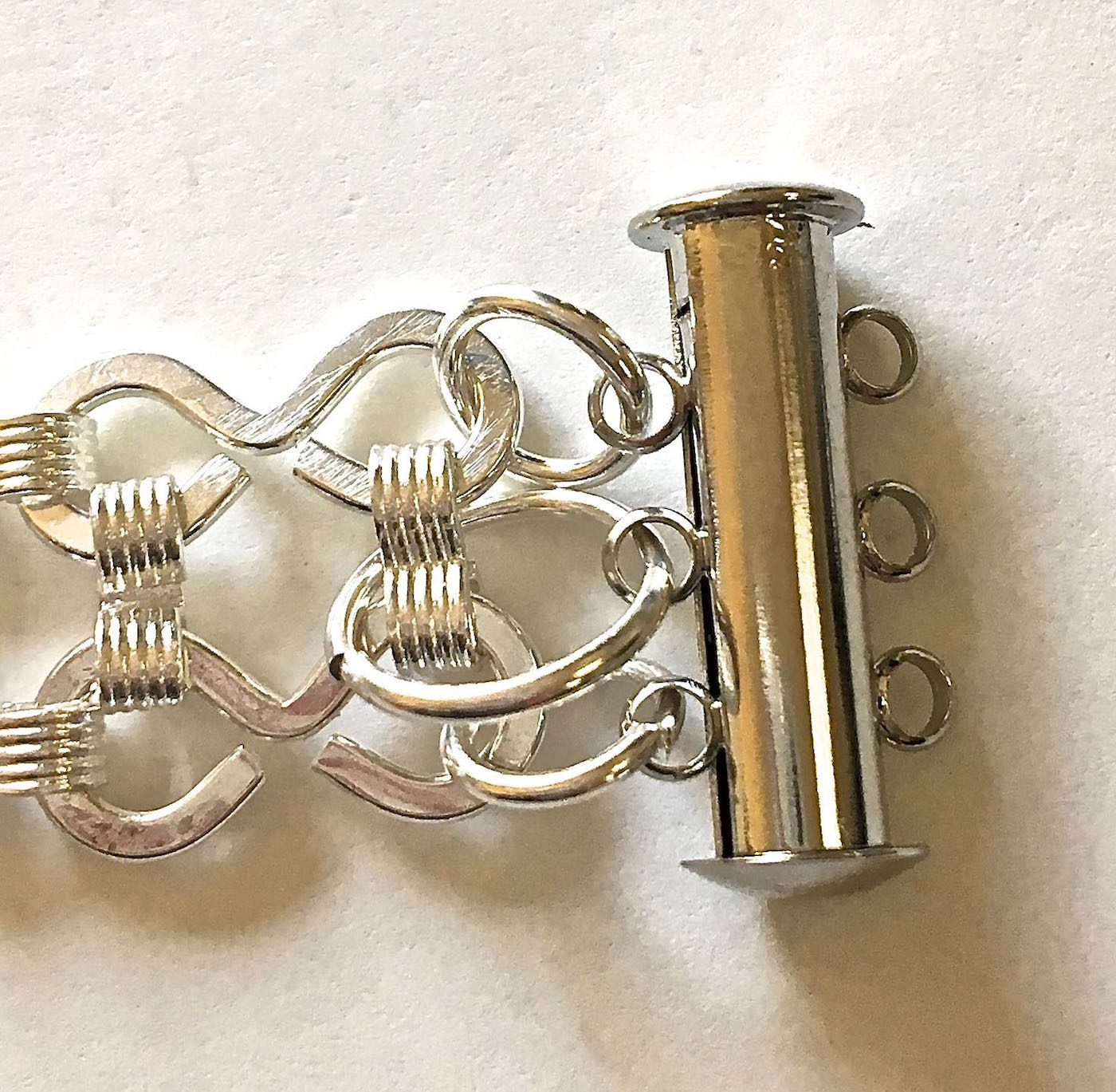 step 9 - Attach Strands One, Two and Three to jump rings in that order. Attach toggle clasps to the jump rings.