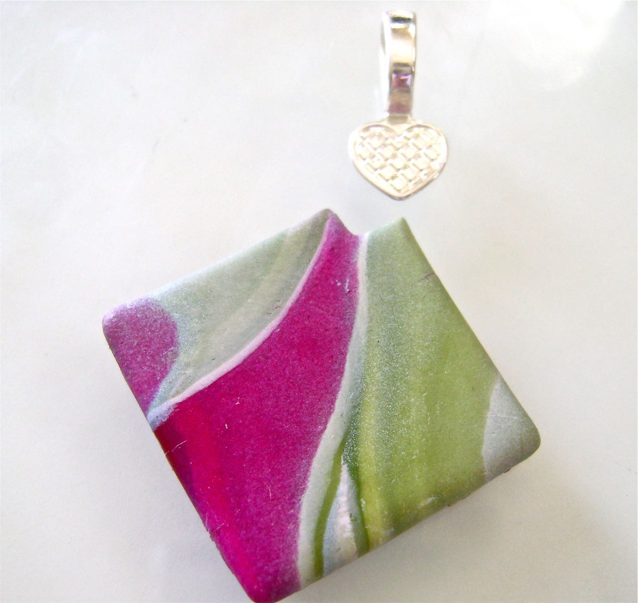 step 10 - Cut a notch from one corner of the square so it will hug the pendant bail later. Bake the beads and pendant in a 275 degree oven on a parchment lined flat baking sheet. Allow to cool completely before handling.