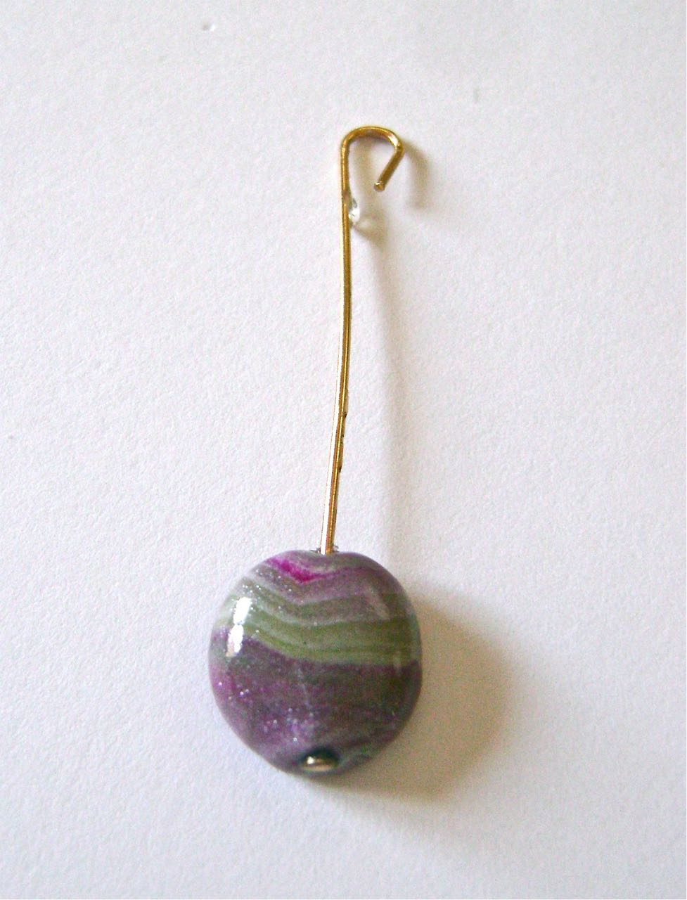 step 11 - Glaze the beads by slipping them onto nail head wires. Curve the top of the wire to create hooks for hanging. Fill a small container with Diamond Glaze and dip each bead into the glaze. Hang on a wire clothes hanger with protective plastic beneath to catch drips.
