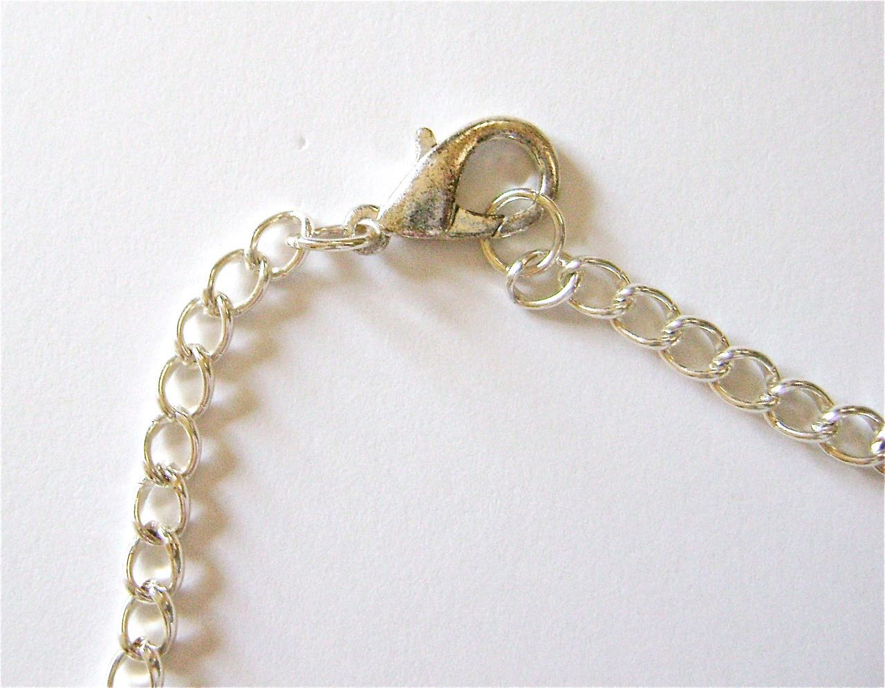 """step 15 - Attach a 5.5"""" length of chain to the hook of each clam shell. Attach a lobster clasp to the end of one chain and a jump ring to the other."""