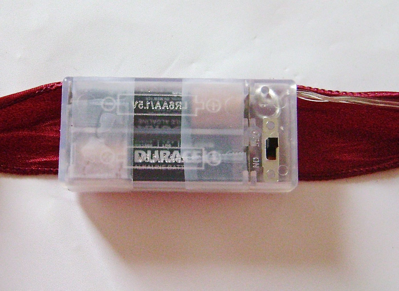 step 6 - Insert batteries into the plastic case and tape the light string battery pack to the center of your ribbon.