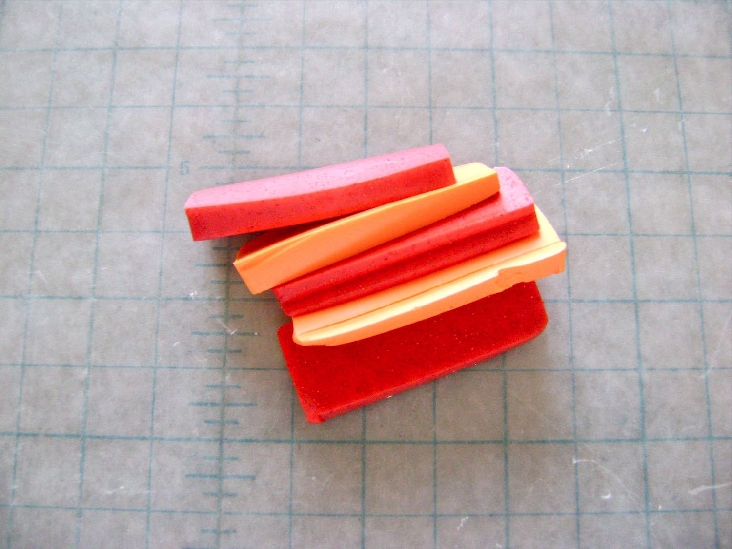"step 1 - Cut the orange and pink clay into thin slices and condition.  Blend them together with a roller or pasta machine to create the watermelon color.  Cut the clay into a 1.25"" x 7"" strip, or the size that will fit your round cookie cutter.  Wrap heavy-duty foil around the cutter followed by the clay strip.  Adjust the size if necessary.  Blend the ends together to create a ring."