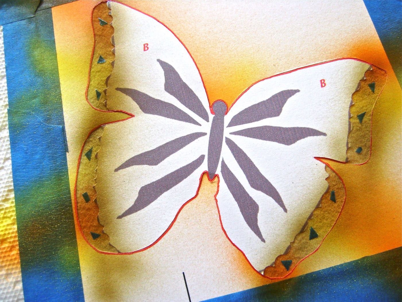 step 8 - With regular scissors, cut a few tiny odd shapes from painter's tape and adhere them to the exposed wing borders. Paint the borders with a light spray of Bronze Have More Fun paint.