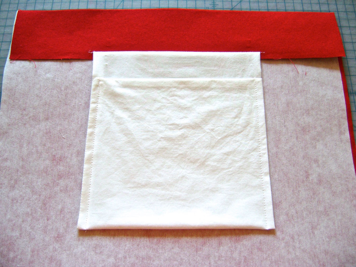 "Attach pockets if you choose to. Make them simple by sewing three sides of a 8.5"" white cotton square. Turn it right side out then fold the bottom up to within 2"" of the raw edge. To finish, sew down the sides then bast the raw edge of the pocket to the bottom raw edge of the tote hem."