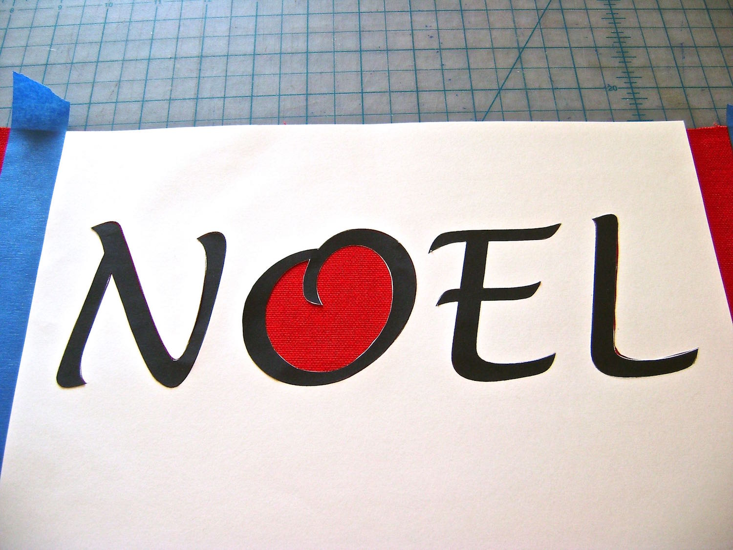 step 7 - Place the four die-cut letters into position on the Noel stencil.  Press down all the edges until they securely adhere to the fabric.
