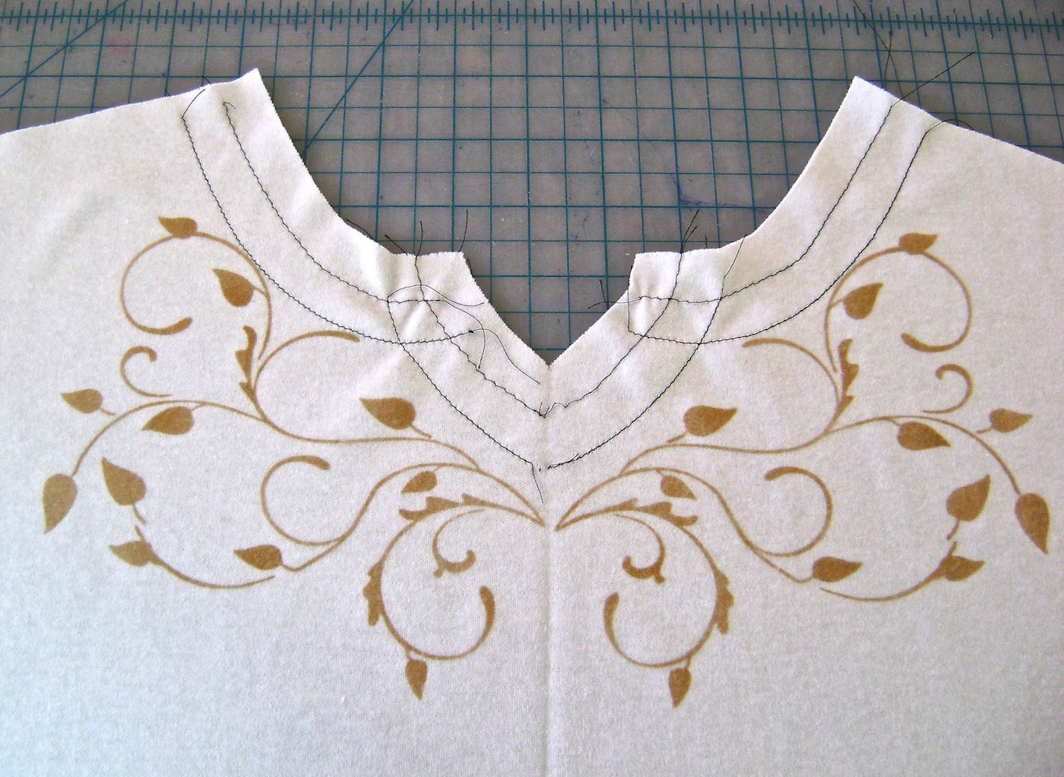 step 7 - Remove paint from the stencil then apply adhesive spray.  Repeat step #4 and # 5 with the stencil flipped to create a mirror image of the painted fabric.