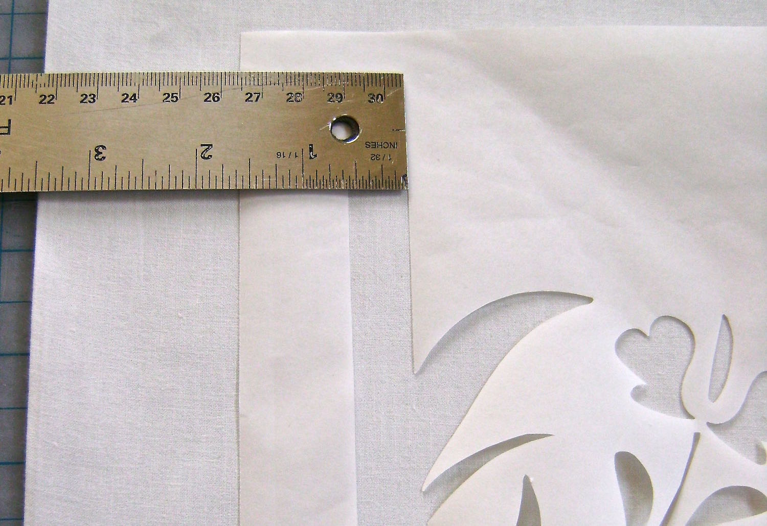"""step 4 -  Pillow Front   Cut out a square of white fabric measuring 13.25"""". Place the Freezer Paper wax side down on the fabric. Position the black vertical line of the stencil 3.5"""" from the left edge of fabric."""