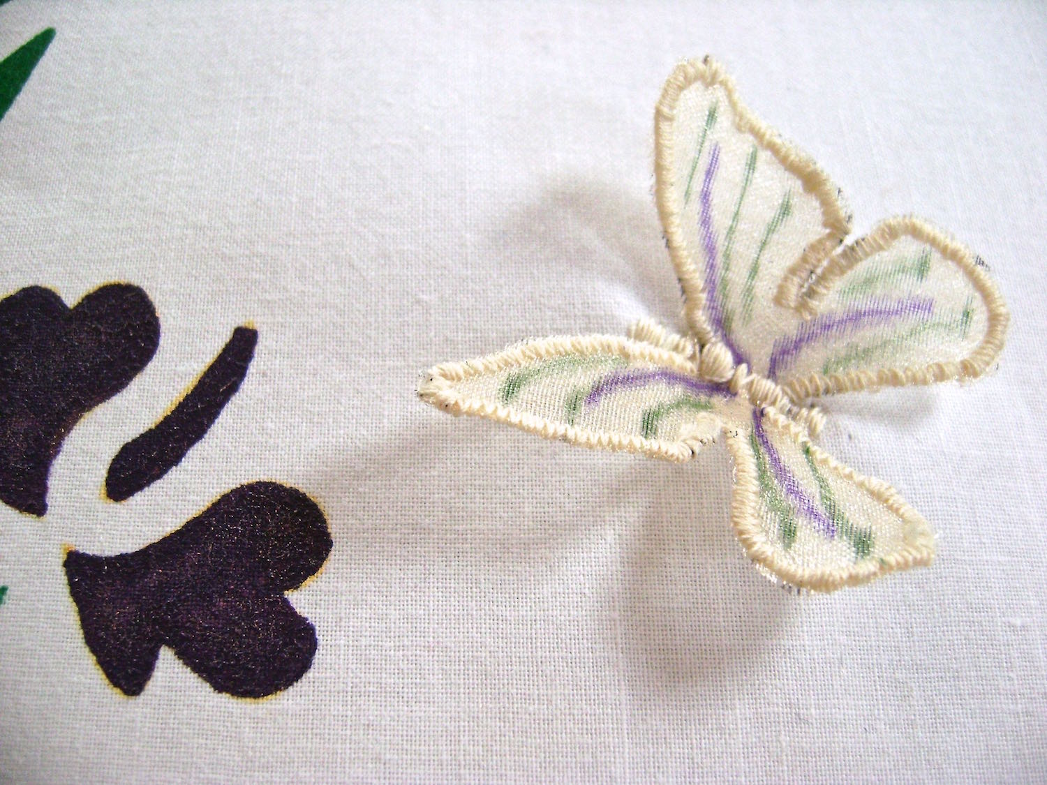 step 19 - With sharp scissors, cut away organza outside stitching line and position the butterfly wings on the pillow front. Sew down the center of the butterfly with the same zigzag stitch you used for the wings, to create the butterfly body.