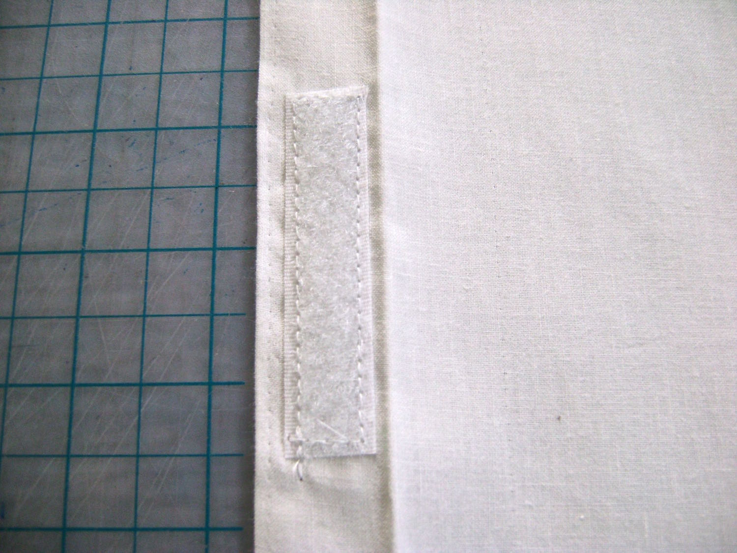 """step 22 - On one piece, sew one half of a 3"""" Velcro strip to the center of the hem. Fold the 1"""" hem over again and sew close to the edge the entire length of the fabric. The piece should now measure 7.75"""" x 13.25."""
