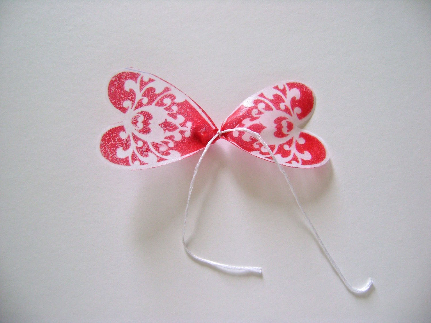 """step 8 - I've used photos of the Valentine flower for these steps because they are clearer. Tie the center of each petal section with a string and a double knot. Leave the string tails about 3"""" long."""