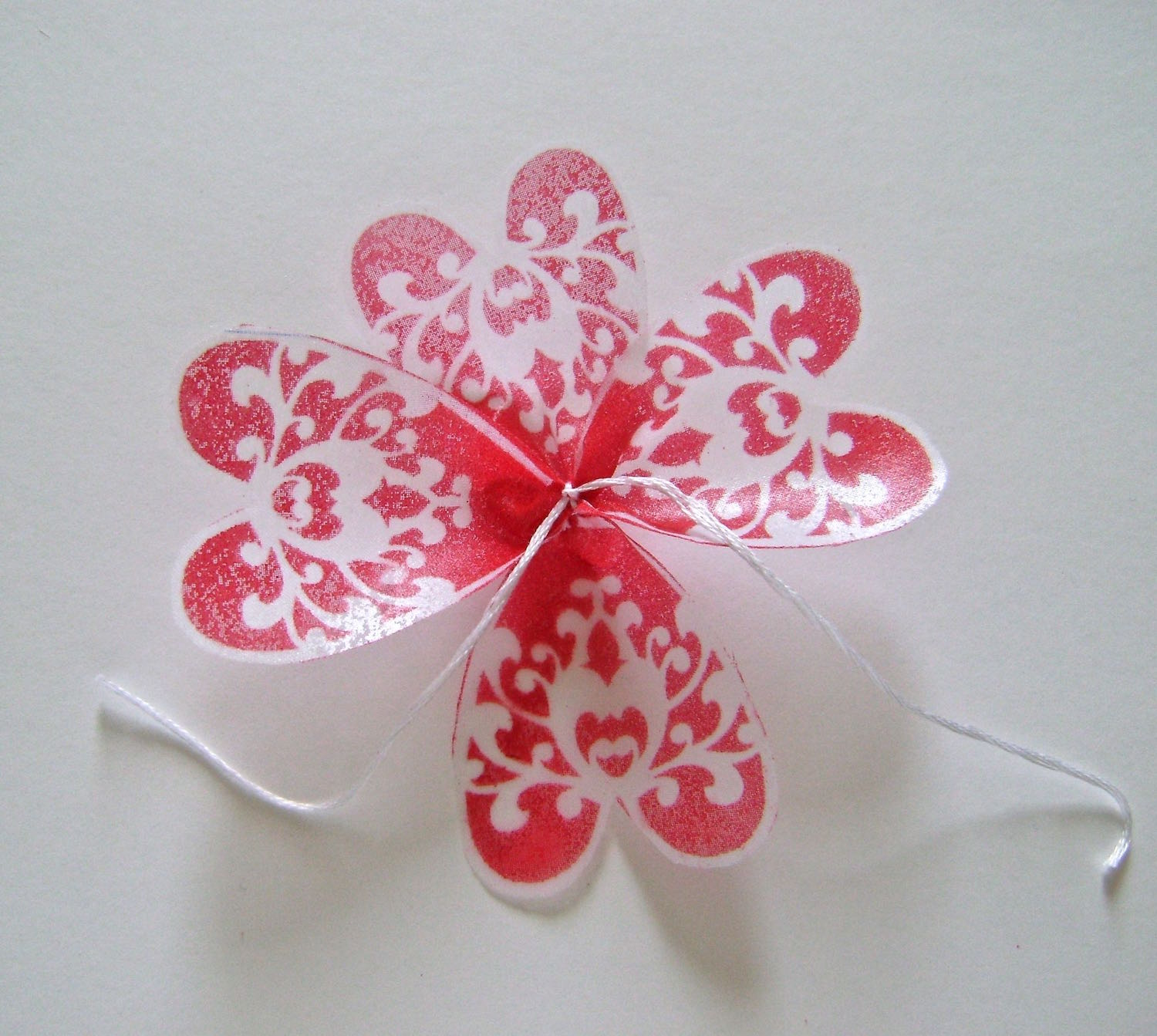 step 9 - To assemble the flower, stack the petals with the largest on the bottom and the smallest on top. Stack each section in a different direction than the one below it. Each time you add another section, tie the string tails under the section below it. Knot the string and cut off the tails.