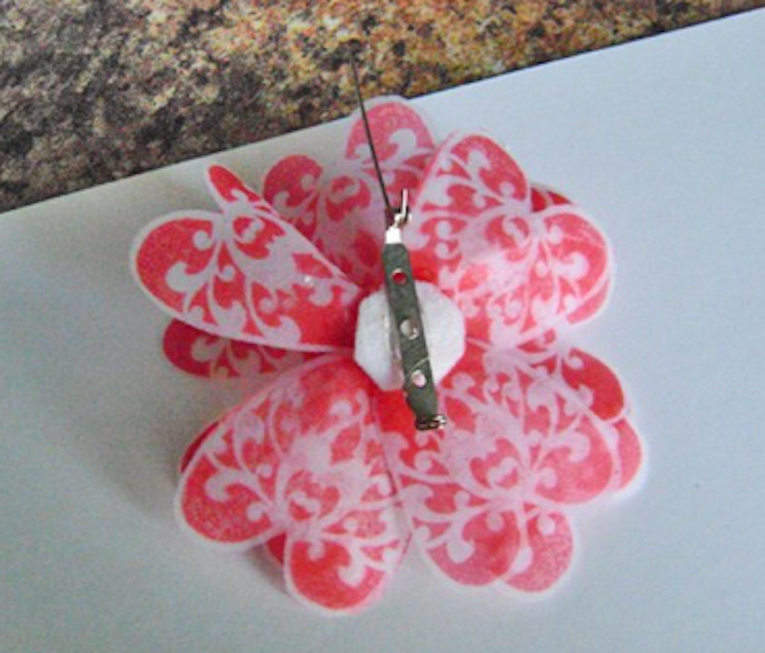 step 10 - Turn the flower bottom side up and glue a small circle of felt or fleece over the knot with Fabri-Tac. Use Dazzle-Tac or other jewelry glue to attach a pin.