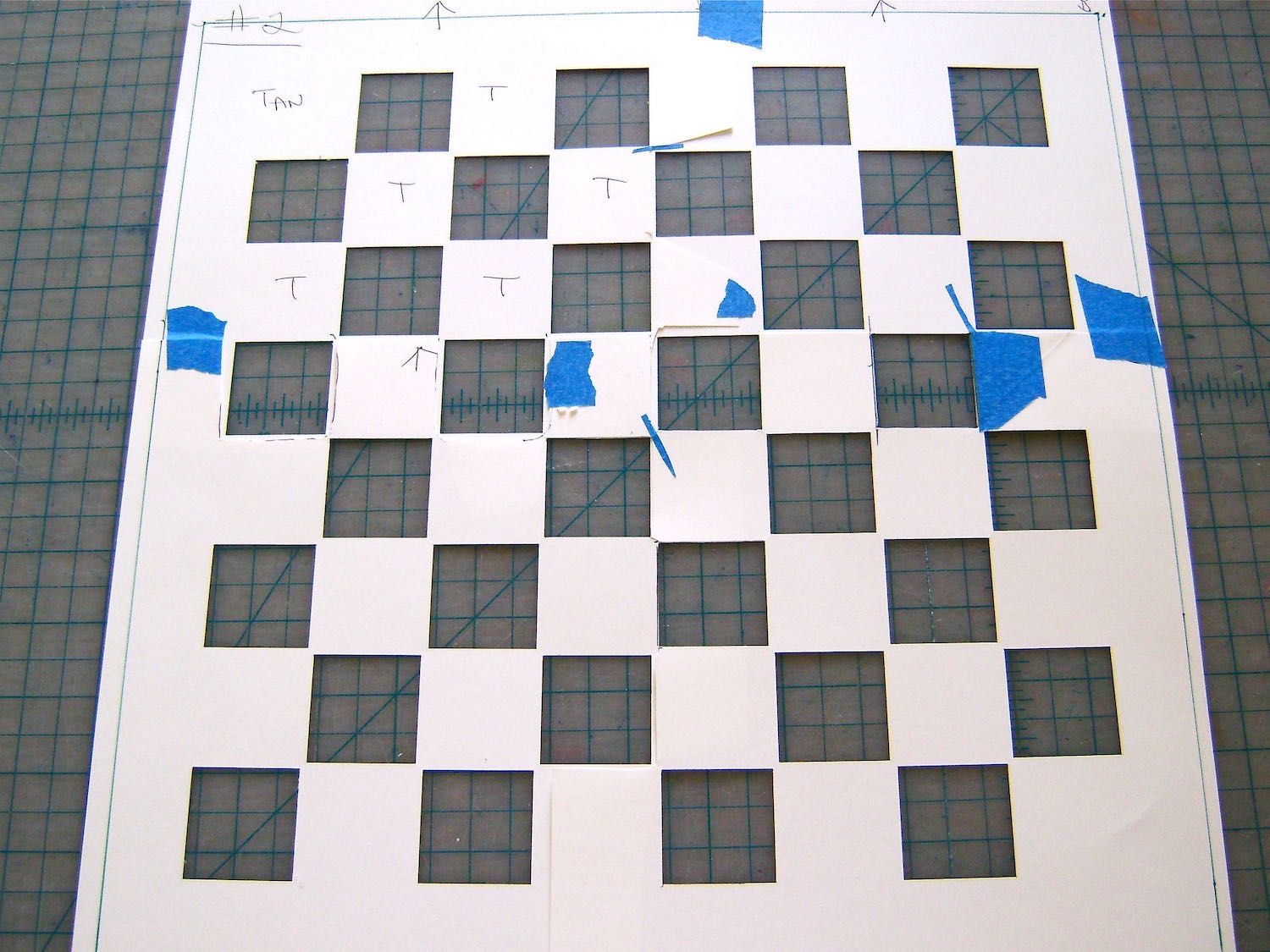 """step 2 - Tape the copies together allowing a one-inch border on the four outer edges. The thin black lines indicate the edges of the playing board area. Once taped together, the playing area should measure 12"""" square. The complete card stock template should measure 14"""" square. With a craft knife and ruler, cut out all the black squares."""