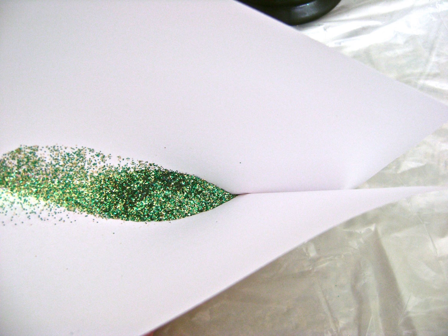 step 9 - To return glitter to the container, create a crease on one end of the paper, forming a funnel.  Hold it over the container and the glitter will slide down the crease. Coat and Create takes 24 hours to set.  Avoid touching the glitter areas as you continue working.