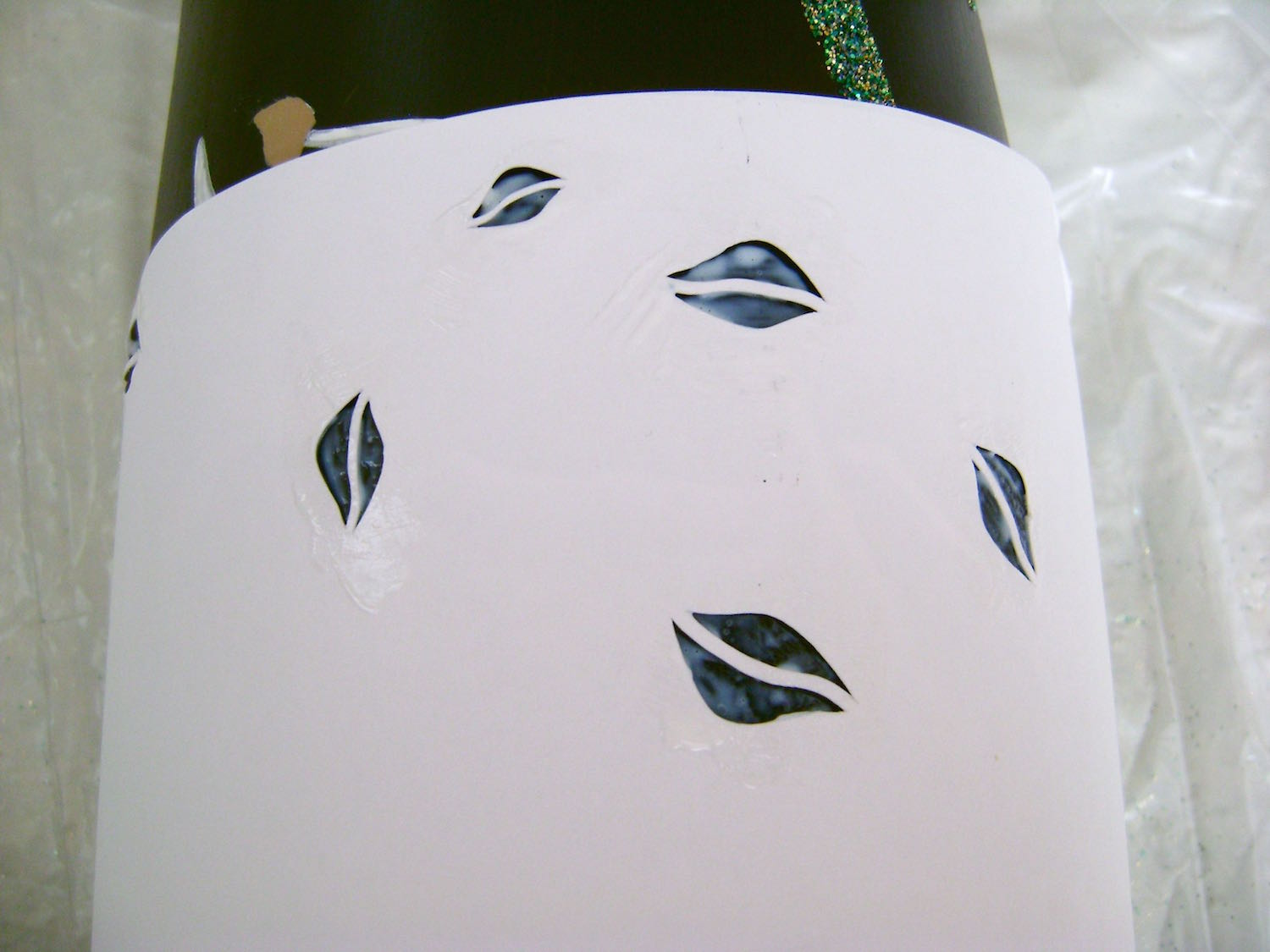 step 14 - Trim the leaf stencil and remove the backing on the side edges.  This will help to hold the stencil against the vase.  Don't allow the sticky back to come in contact with paint as it could lift paint when removed.  Apply Coat & Create to the leaf openings.