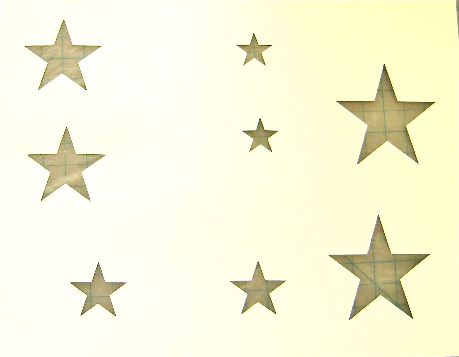 step 1 -  Draw stars in three different sizes on card stock and cut them out with a craft knife.