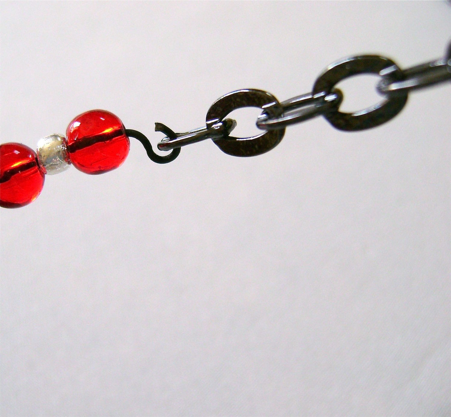 step 23 - Insert the open loops of the bead sections into the end links on the chain sections and close the loops.