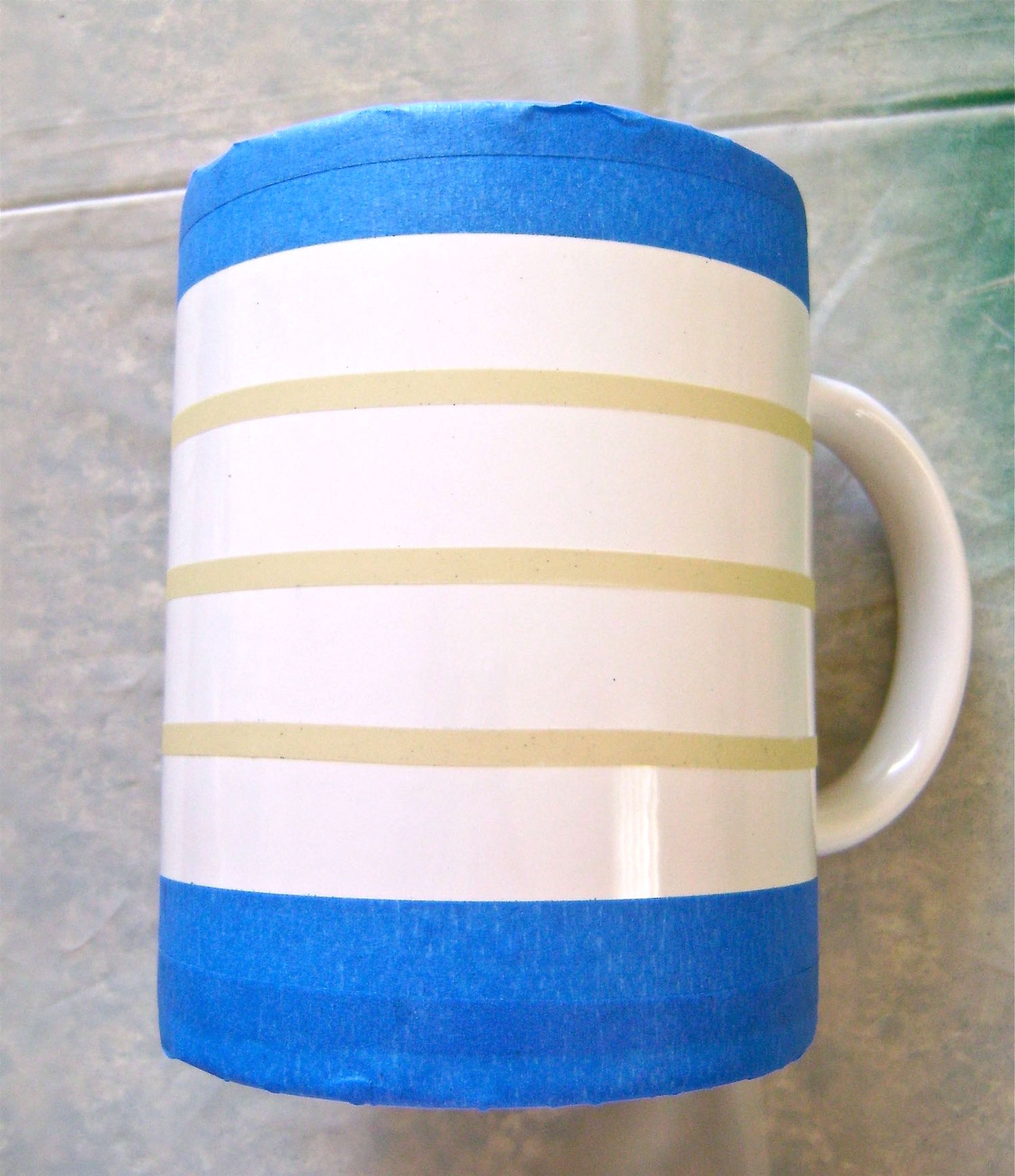 """step 4 -Measuring 1"""" from the edge of the top masking tape, place ¼"""" tape around the mug, stopping at the vertical tapeline. Place two more lines around the mug positioned 1"""" apart."""