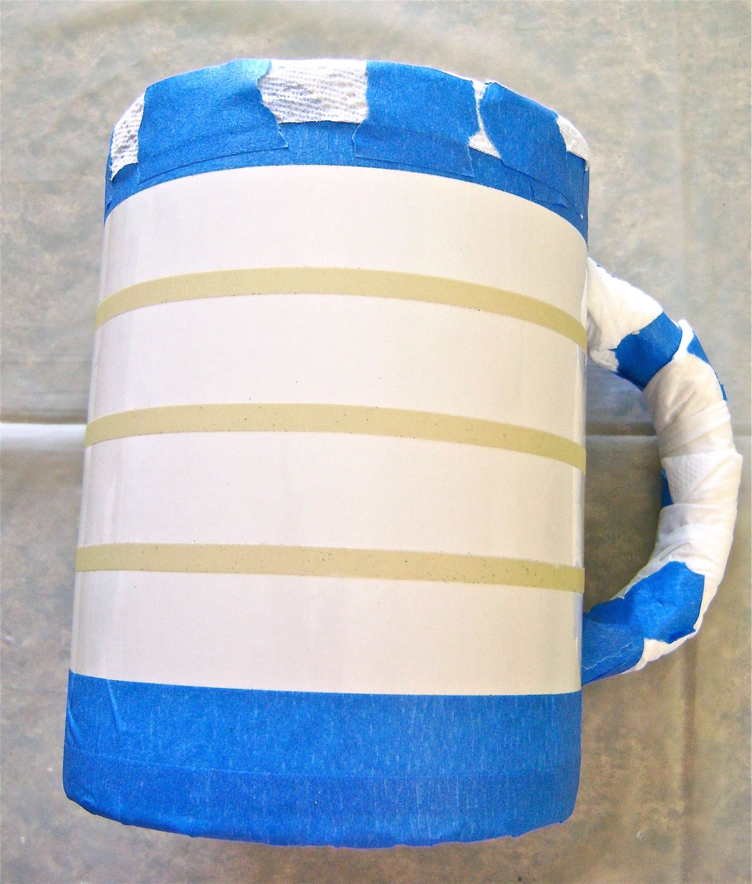 step 5 - Mask the inside of the mug with a paper towel.  Tape the edge of it to the top edge of the mug.  Wrap tissue around the mug handle.
