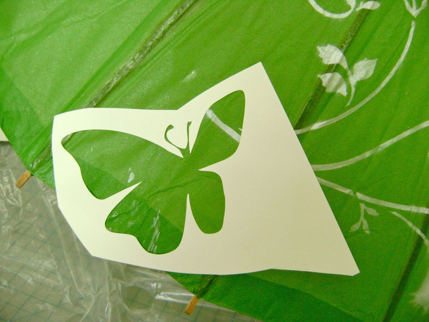 step 4 -Download and print out the butterfly stencils on card stock.  Cut out the images and spray the backside with adhesive.  Position one butterfly in each parasol section, alternating small and large and their placement on the parasol.