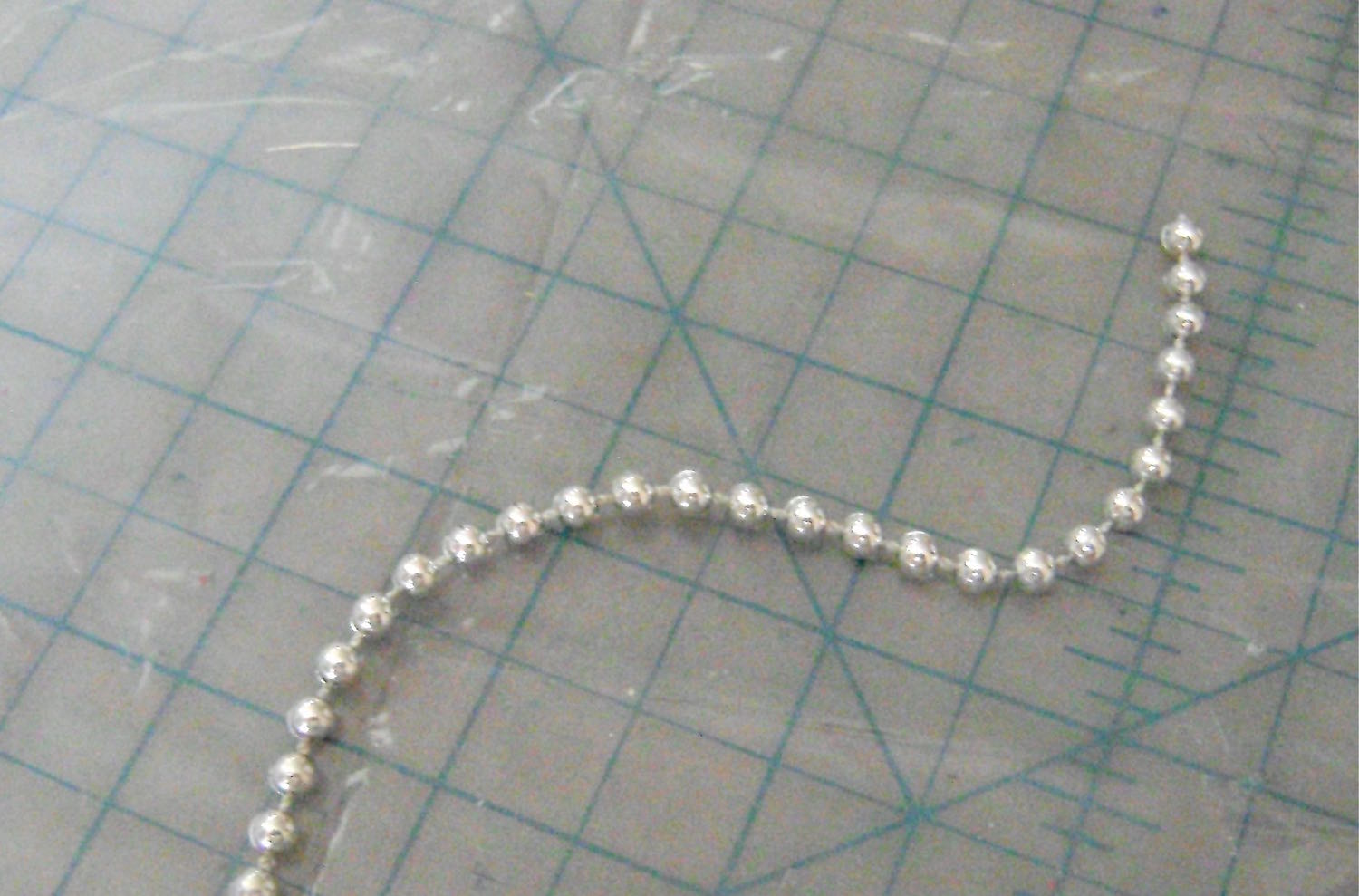 step 10 -  Cut a strip of silver beads to fit around the center top of the parasol and glue it in place with Jewel-It.