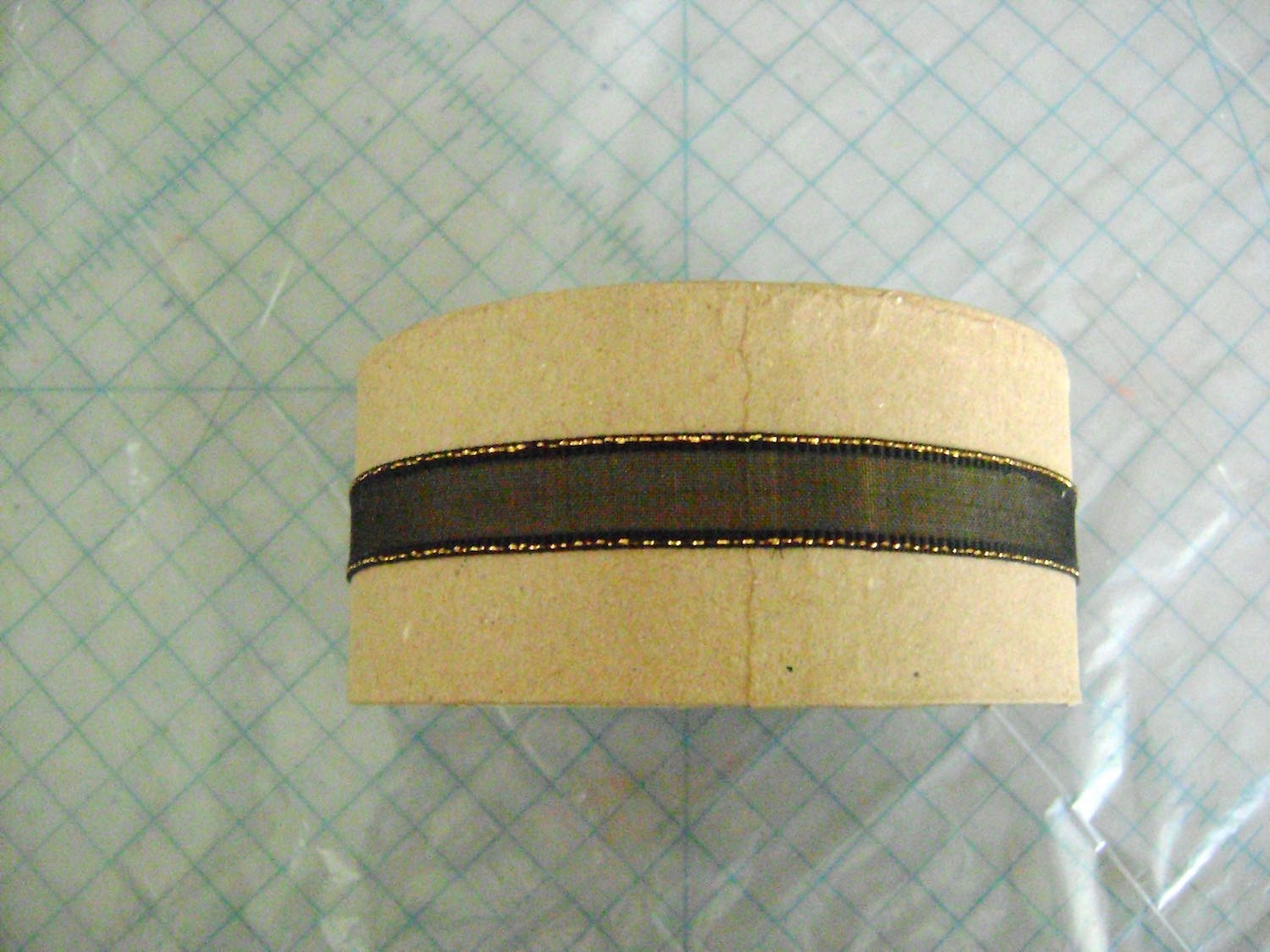 """step 9 - Cut a 14"""" long strip of ribbon. Line it with double-sided adhesive tape and press it around the box cover. Attach a decorative button over the ribbon seam with E-6000 glue."""