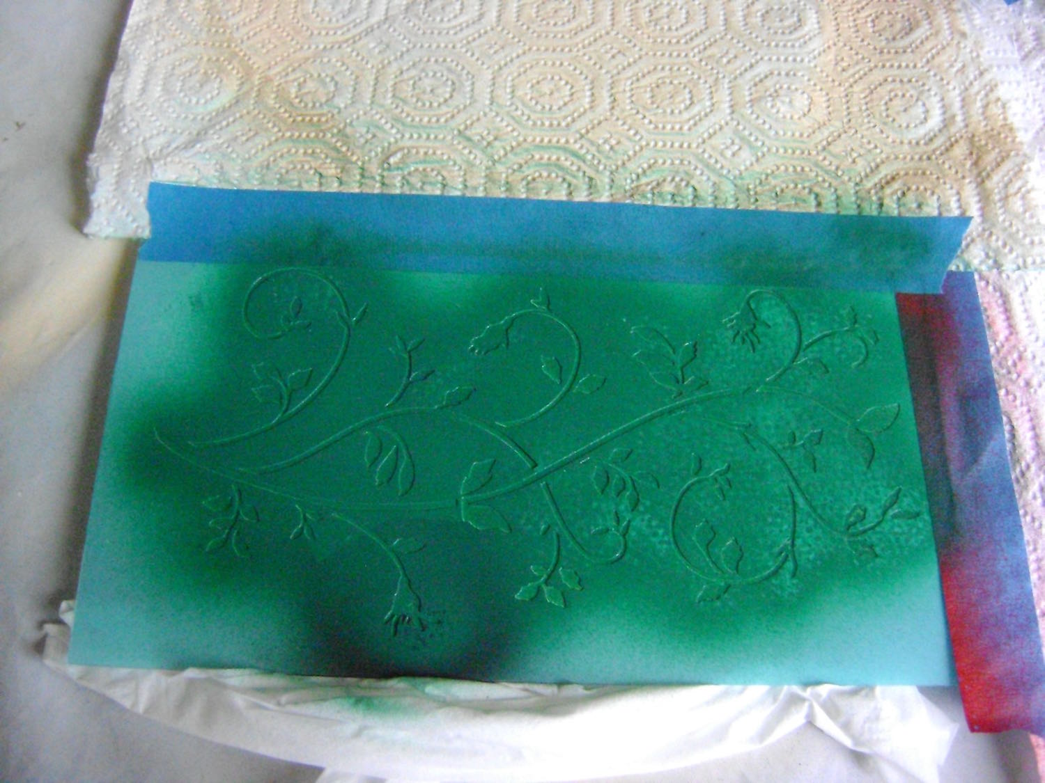 step 9 - Spray the back of the floral stencil with adhesive.  Place it across the painted plaque.  Airbrush it with green paint mixed with a bit of red to deepen the color.  Allow to dry then remove the stencil.