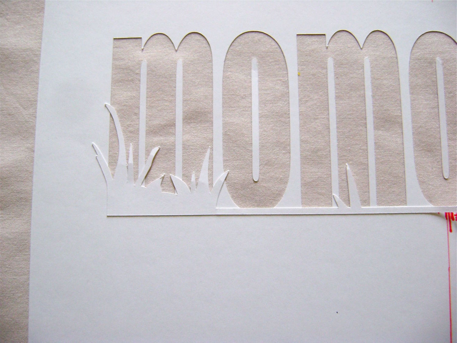 step 5 - Apply Spray Mount adhesive on the back of the die cut grass piece. Center, align, and press the piece onto the Mom stencil. The bottom edge of the grass piece should be flush against the bottom of the Mom lettering.