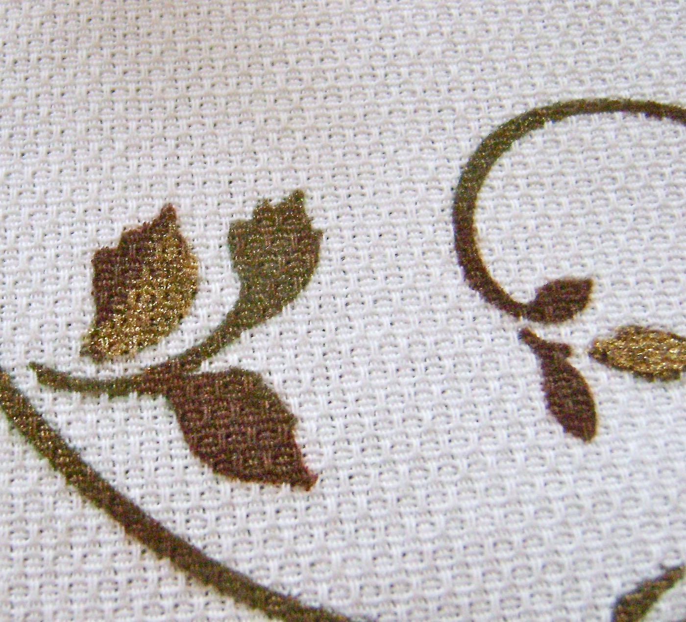 step 13 - Finish the runner by applying gold paint to some of the leaves and stems using a brush.  Layer the decorative runner on top of the burlap runner and arrange them on the table.