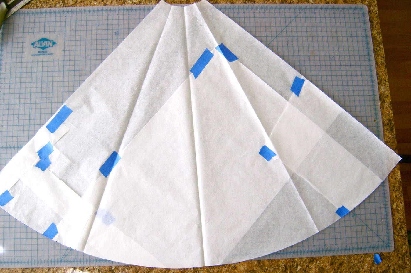 step 7 - Connect the dots creating the cutting line for the pattern bottom. Cut on the curved line. Unfold the pattern piece. This represents a quarter of the tree skirt. Use this pattern to cut out four identical pieces of fleece.
